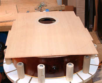 The new top has been joined, a reproduction rosette inlaid (the original had cracked from age and could not be reused) and the outline drawn.