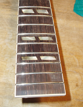 The neck was stripped, re-bound, and is now ready for finish. Due to heavy playing wear, the fingerboard was resurfaced, and the inlays re-fitted. The frets were fitted over the binding at the customer