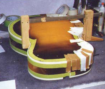<p>The binding on the entire guitar was falling apart into dust, among other issues. Here the guitar has had the top and side joints reglued and aligned, the neck removed, and reproduction binding is being glued and clamped. The tape protects the finish from the solvents in the binding cement.</p>