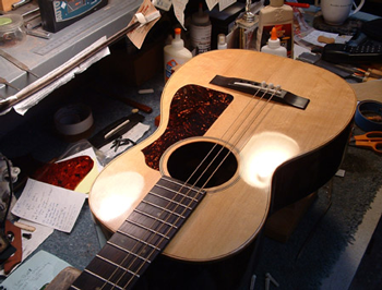 The French Polish is cured, the new hand-cut pickguard is applied, and the strings are going on. The shellac gives incredible depth and shine to the Sitka Spruce top.